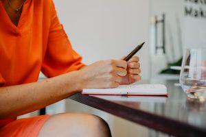 een vrouw met een pen in haar hand leunend op een boek