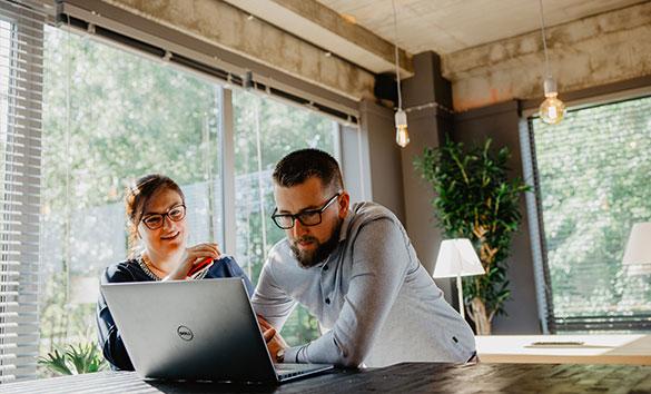 2 personen die communiceren en naar een laptop kijken