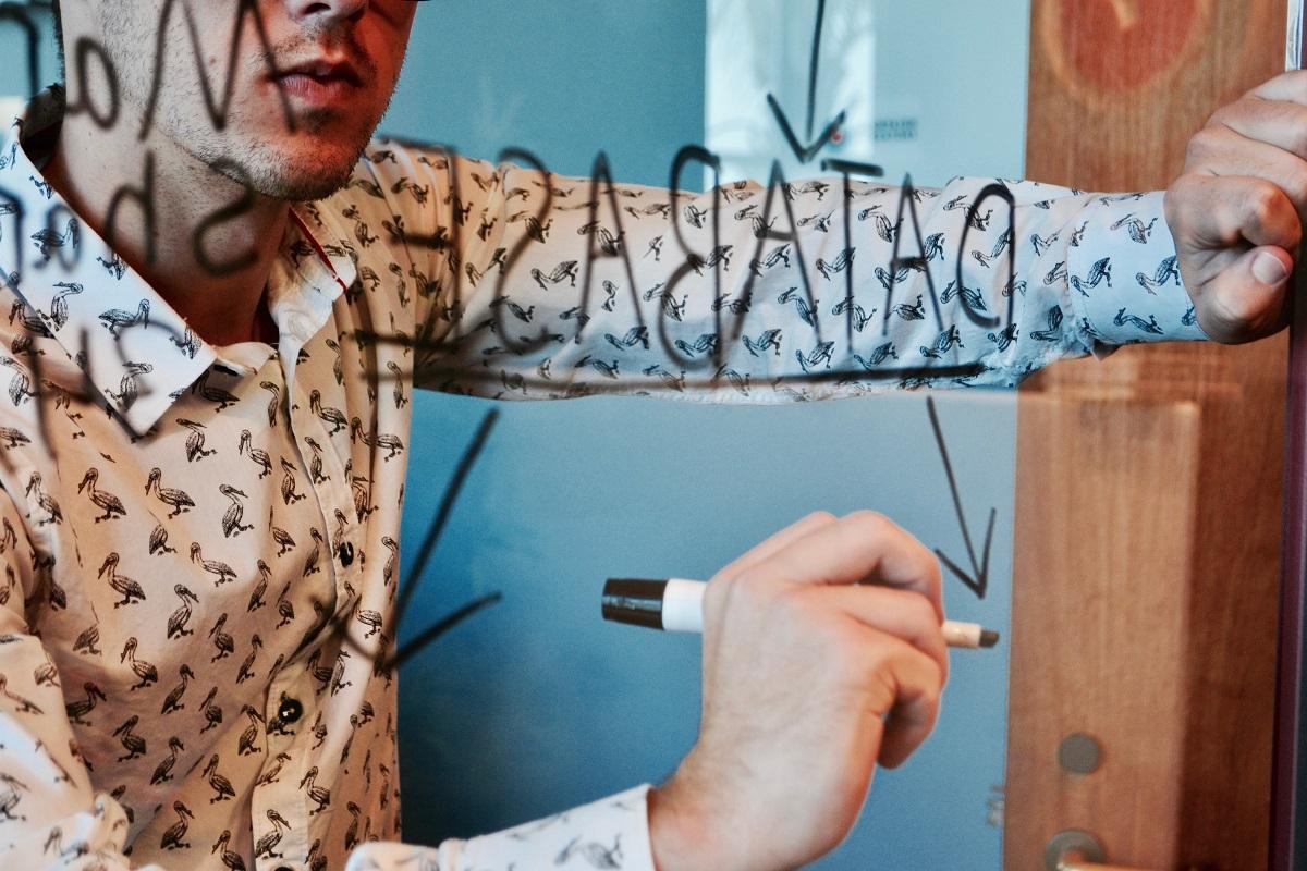 Iemand die iets met een stift op een glazen muur schrijft